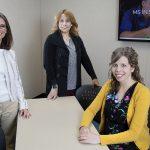 Three staff members of the Speech-Language Pathology program surround a classroom table smiling.